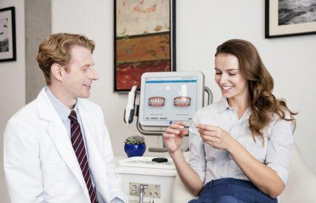 """Tandlægen og en patient der kigger på den """"usynlige"""" skinne der bruges til tandregulering"""
