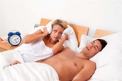 En mand der har brug for en snorkeskinne, da hans snorken holder hans kæreste vågen